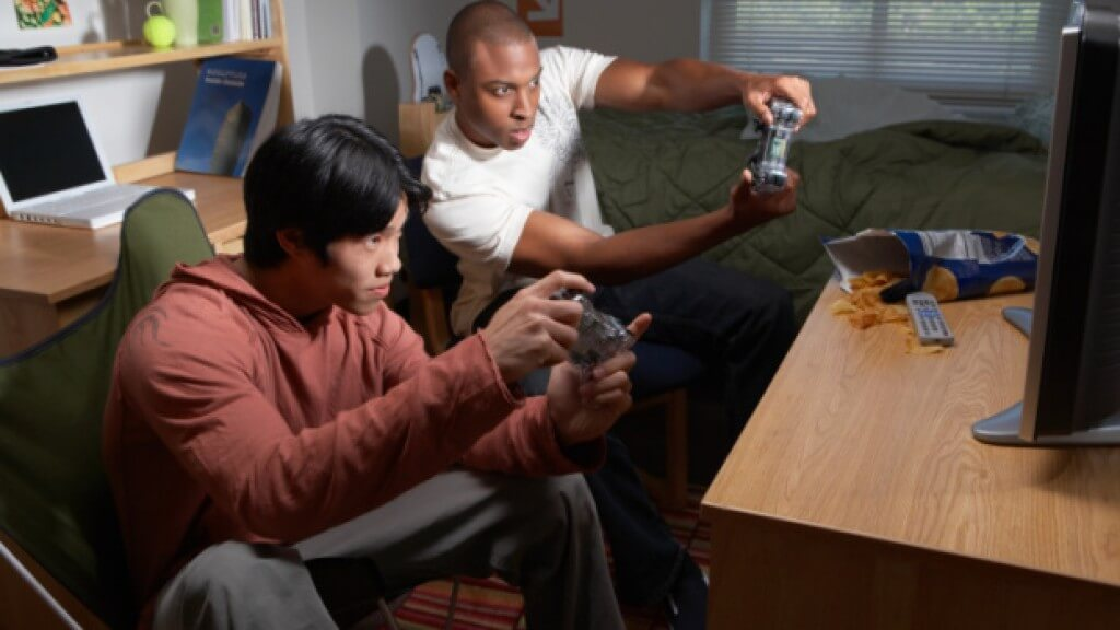 Two young men playing video games on TV in dorm room
